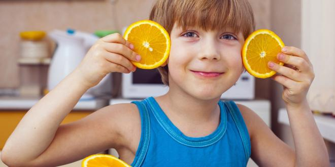 child with oranges